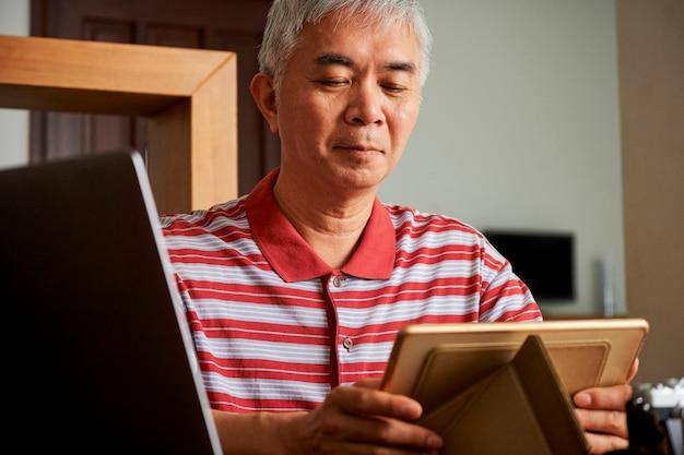 Homem colocando tablet no suporte