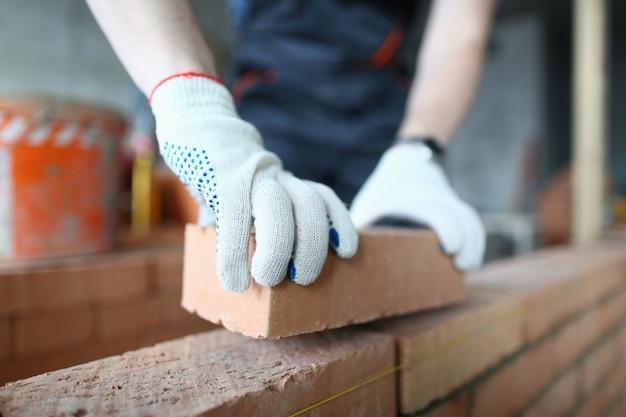 Homem colocando tijolos