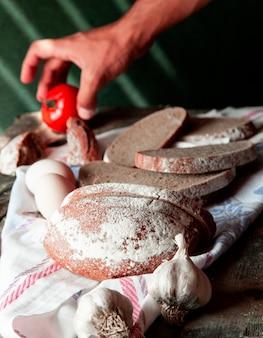 Homem colocando tomate numa toalha de mesa branca com fatias de pão, ovos e alho luvas ao redor.
