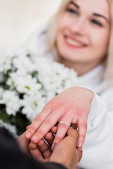 Homem colocando um anel de noivado de diamante no dedo de sua noiva