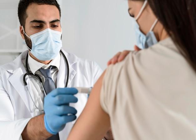 Homem colocando um curativo no braço de um paciente