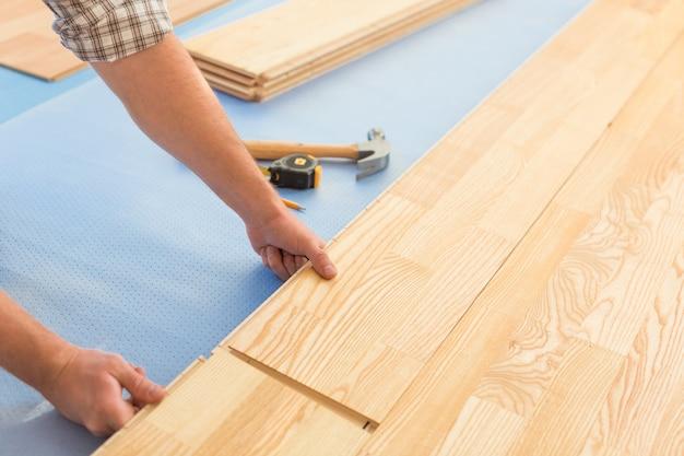 Homem colocando um novo piso de tábuas, close-up