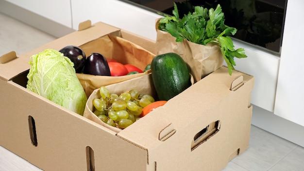 Homem colocando um recipiente de papelão marrom com vários vegetais no chão em close-up da cozinha