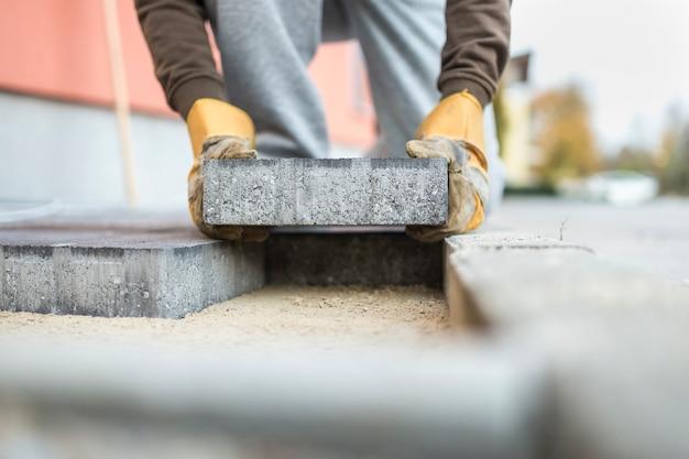 Homem colocando um tijolo de pavimentação, colocando-o sobre a fundação de areia