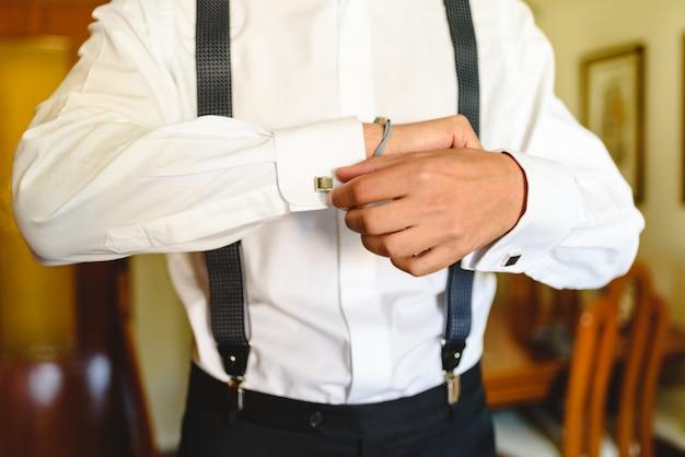 Homem colocando uma camisa branca para vestir elegantemente.