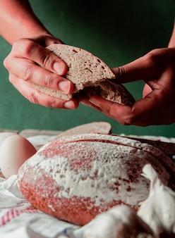 Homem colocando uma fatia de pão preto na mão.