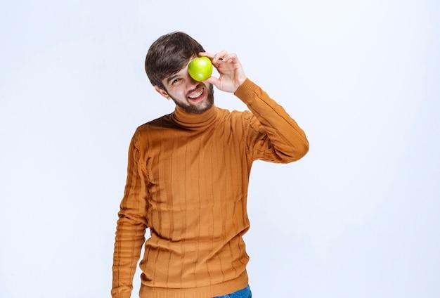 Homem colocando uma maçã verde no olho.
