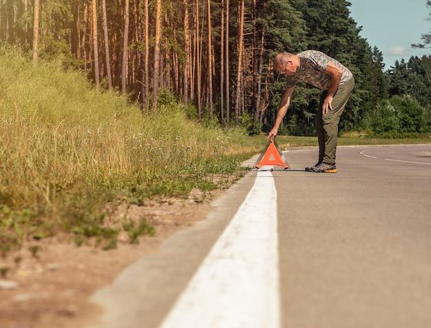 Homem colocando uma placa de advertência de triângulo vermelho na beira da estrada na natureza