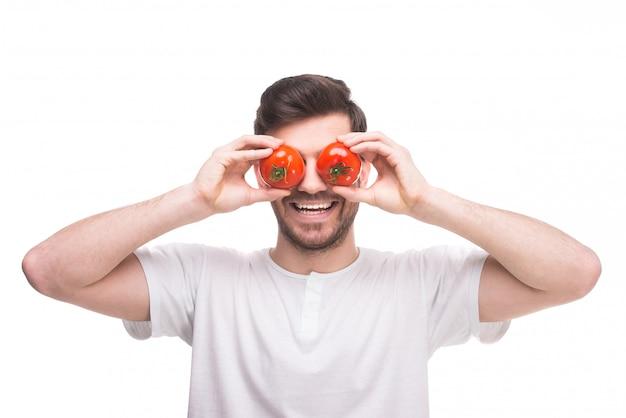 Homem colocar tomates em seus olhos e sorrisos.