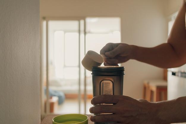 Homem colocou proteína de soro de leite em pó no frasco de batido.