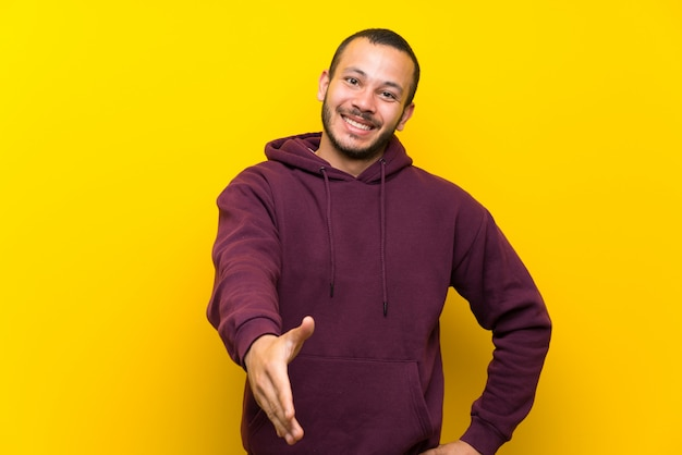 Homem colombiano com moletom sobre parede amarela, apertando as mãos para fechar um bom negócio