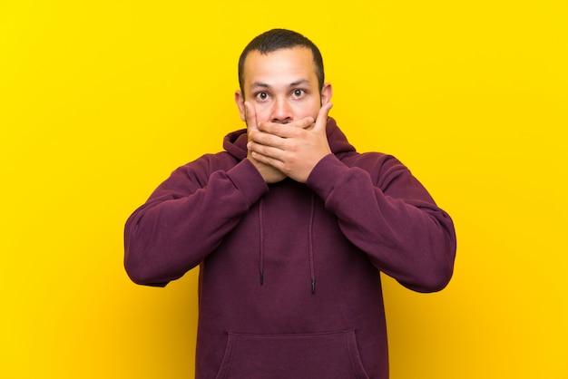 Homem colombiano, com, moletom, sobre, parede amarela, coberta, boca, com, mãos