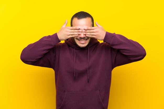 Homem colombiano, com, moletom, sobre, parede amarela, coberta, olhos, por, mãos