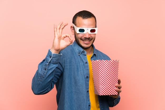 Homem colombiano com pipocas mostrando um sinal de ok com os dedos
