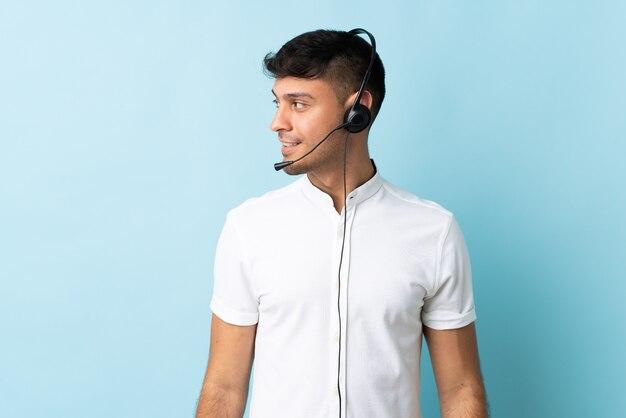 Homem colombiano de telemarketing trabalhando com fone de ouvido em um lado isolado