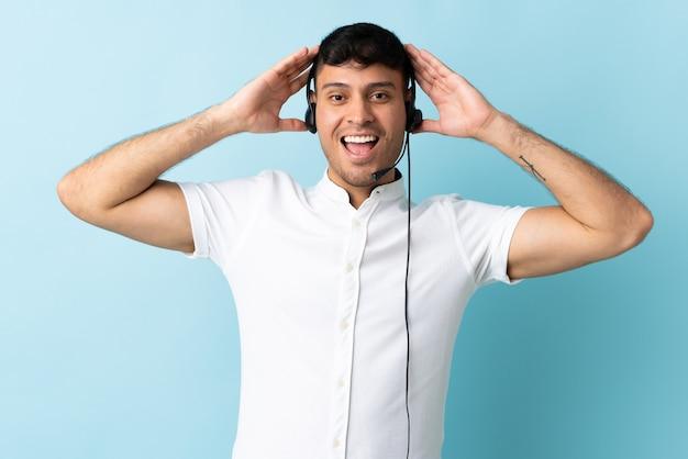 Homem colombiano de telemarketing trabalhando com fone de ouvido isolado com expressão de surpresa