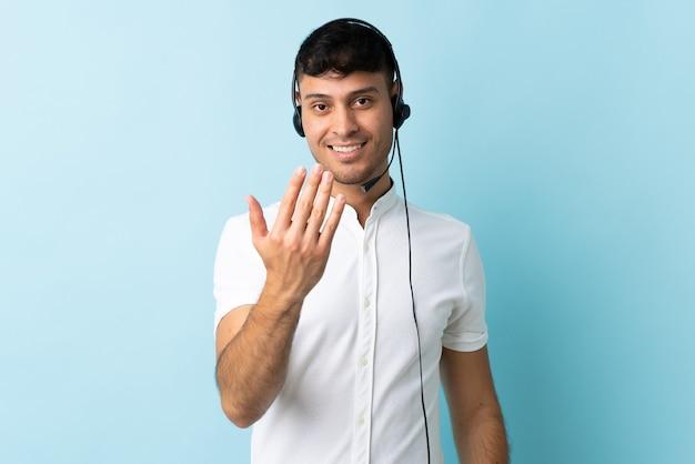Homem colombiano de telemarketing trabalhando com fone de ouvido isolado, convidando para vir com a mão. feliz que você veio