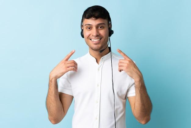 Homem colombiano de telemarketing trabalhando com fone de ouvido isolado e fazendo um gesto de polegar para cima