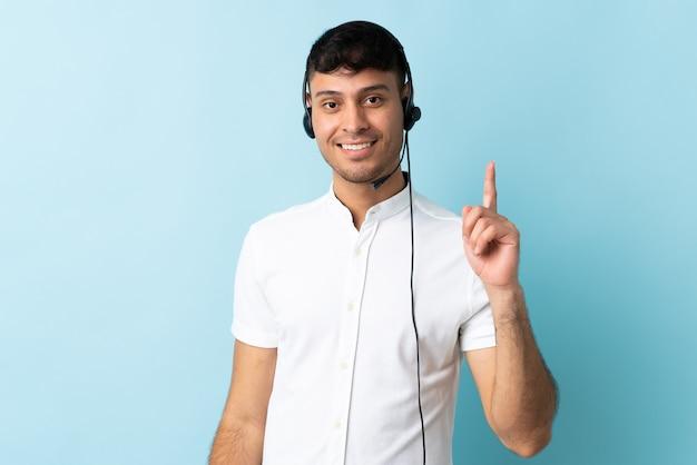 Homem colombiano de telemarketing trabalhando com fone de ouvido isolado, mostrando e levantando um dedo em sinal dos melhores