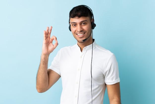 Homem colombiano de telemarketing trabalhando com fone de ouvido isolado, mostrando sinal de ok com os dedos