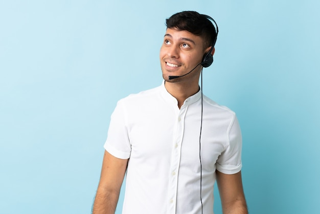 Homem colombiano de telemarketing trabalhando com um fone de ouvido, tendo uma ideia enquanto olha para cima