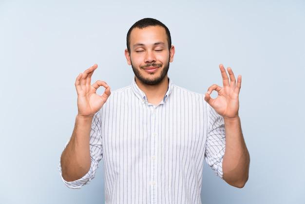 Homem colombiano, sobre, isolado, parede azul, em, zen, pose