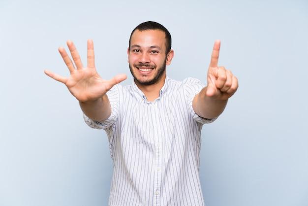 Homem colombiano sobre parede azul isolada, contando seis com os dedos