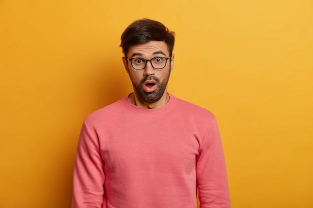 Homem com a barba por fazer assustado e boquiaberto ao ouvir notícias impressionantes