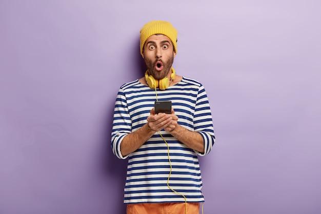 Homem com a barba por fazer chocado e vestido com roupas da moda
