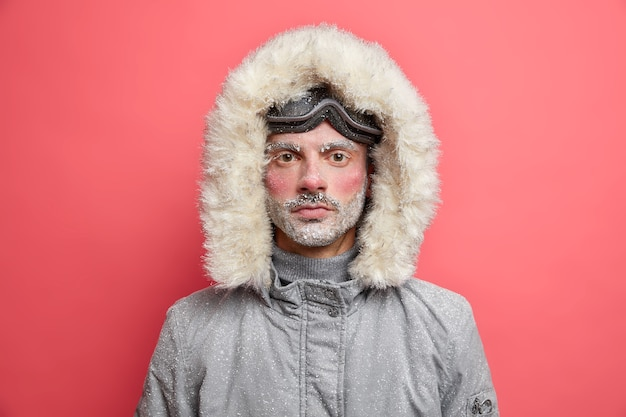 Homem com a barba por fazer congelado, coberto de neve, usa uma jaqueta cinza com capuz.