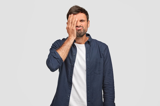 Homem com a barba por fazer descontente incomodou o rosto, cobre os olhos com a mão, sente-se entediado, franze a testa, vestido com uma camisa da moda azul escura, fica de pé contra a parede branca. pessoas e expressões faciais.