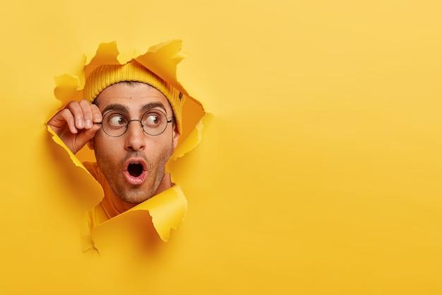 Homem com a barba por fazer espantado olhando pelo buraco no papel amarelo
