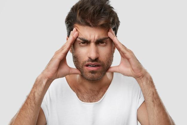 Homem com a barba por fazer exasperado mantém as mãos nas têmporas, tem uma terrível dor de cabeça, sente-se cansado do trabalho constante, tem a barba por fazer