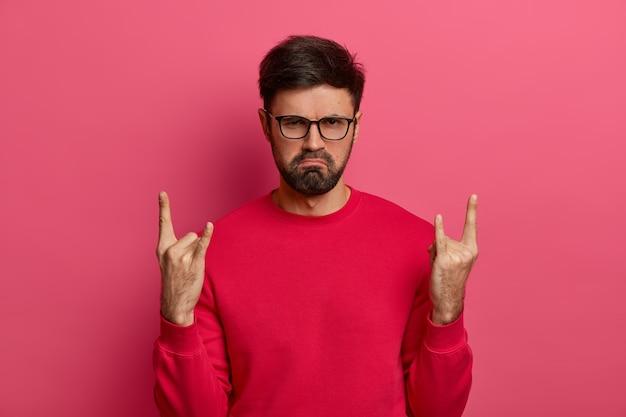 Homem com a barba por fazer insatisfeito e sombrio fazendo gesto de rock n roll
