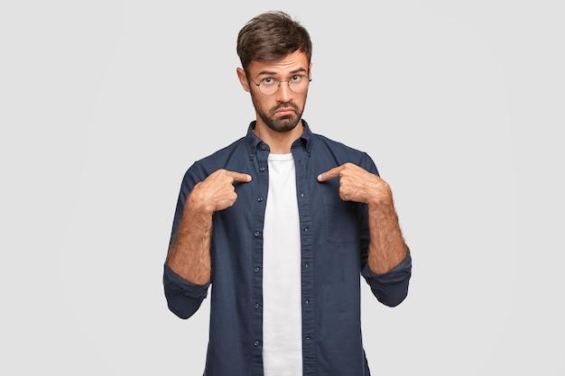 Homem com a barba por fazer perplexo aponta para si mesmo, olha com espanto, vestido com uma camisa casual, franze o rosto, usa óculos, fica maravilhado por ser escolhido para dar palavra, isolado sobre uma parede branca