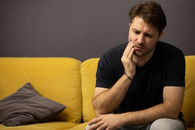 Homem com a barba por fazer sentado no sofá e sofre de dor de dente dentista ajuda no atendimento odontológico