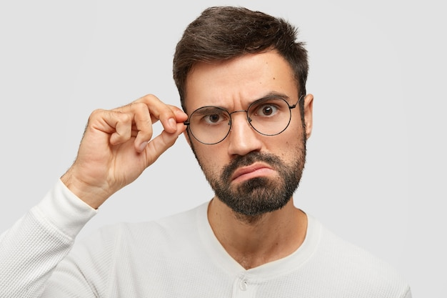 Homem com a barba por fazer zangado olha seriamente para a câmera, franze a testa, toca a borda dos óculos, vê em espanto