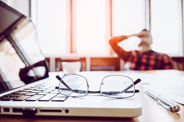 Homem com a mão segurando o rosto fazendo um freio de trabalhar com laptop e notebook com óculos na mesa de madeira. conceito de estresse / repouso / tensão / falha / desencorajamento / depressão