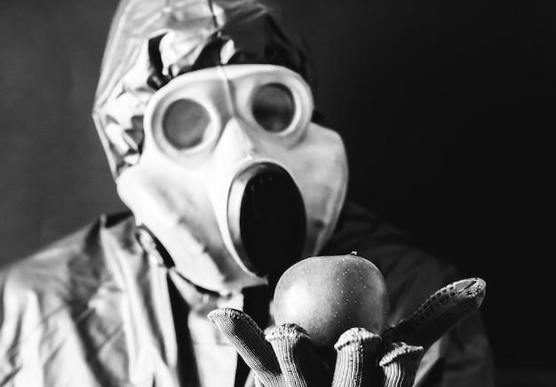 Homem com a máscara de gás segurando a maçã. influência da radiação. poluição ambiental. conceito de chernobyl. energia nuclear perigosa. desastre ecológico.