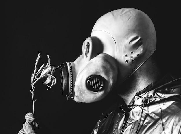 Homem com a máscara de gás segurando uma flor. influência da radiação. poluição ambiental. conceito de chernobyl. energia nuclear perigosa. desastre ecológico.