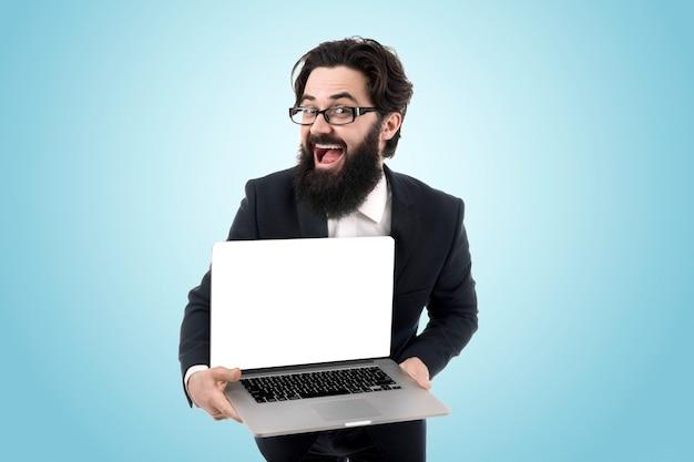Homem com a tela do laptop em branco, jovem barbudo alegre segurando o laptop e sorrindo sobre o fundo azul