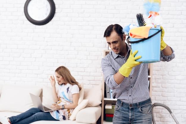 Homem com acessórios mais limpos e mulher no sofá.