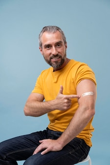 Homem com adesivo no braço após tomar vacina
