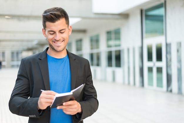 Homem com agenda escrevendo e sorrindo