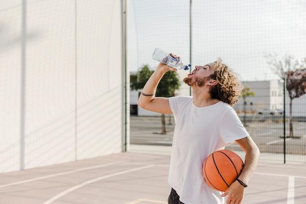 Homem com água potável de basquete