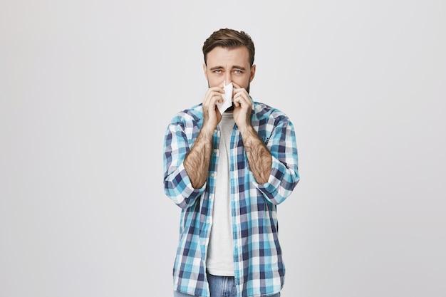 Homem com alergia espirrando em tecido