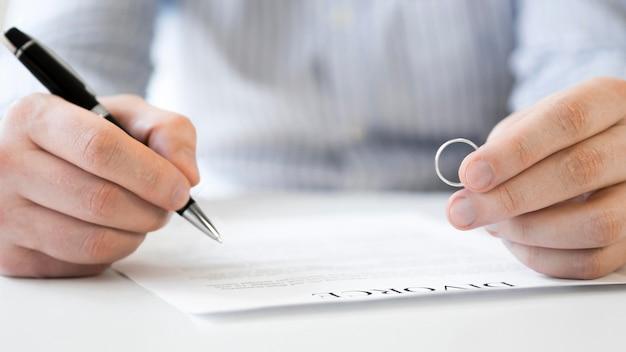 Homem com aliança e contrato de divórcio