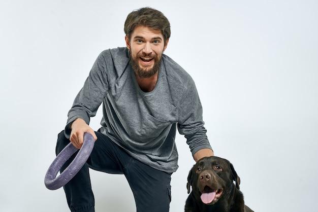 Homem com anel cinza de treinamento de cachorro fazendo animais de estimação de fundo claro de exercícios.