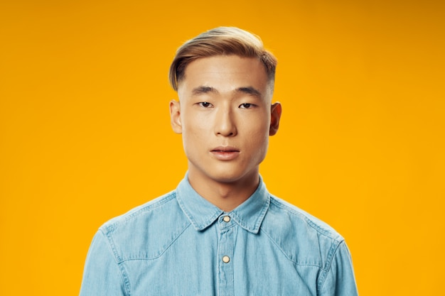 Homem com aparência asiática, penteado elegante, vista recortada, camisa jeans azul amarela