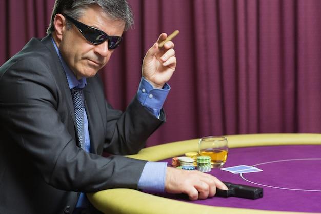Homem, com, arma, em, pôquer, tabela, em, cassino